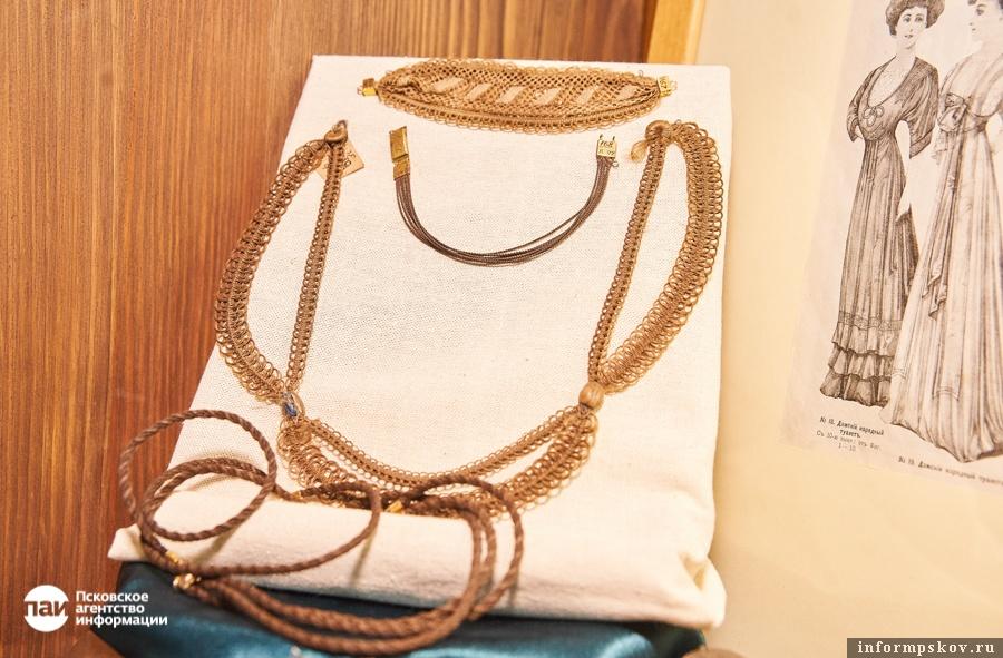 Ажурное ожерелье с золотой подвеской и плоскими пуговицами - в центре снимка