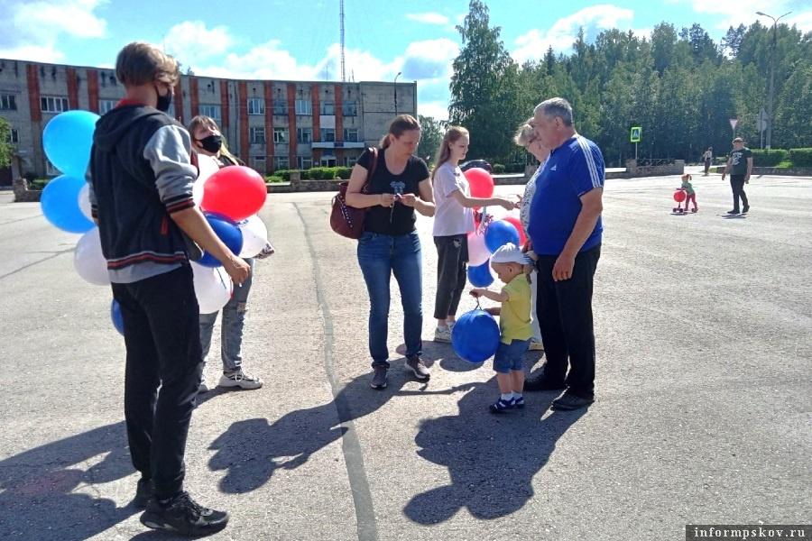Молодёжь раздавала сельчанам шары и ленточки с триколором. Фото газеты «Плюсский край»