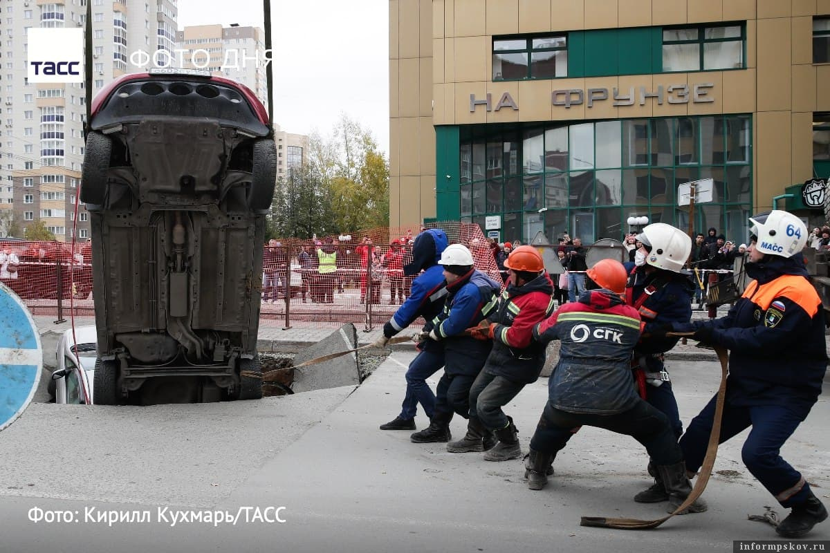 Два авто свалились в провал асфальта в Новосибирске. Фото ТАСС