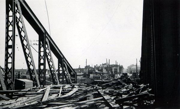 Разрушенный взрывом деревянный настил моста, выброшенный на оставшуюся целой центральную ферму моста.  15 июля 1941 г. Фото из коллекции Вячеслава Волхонского.