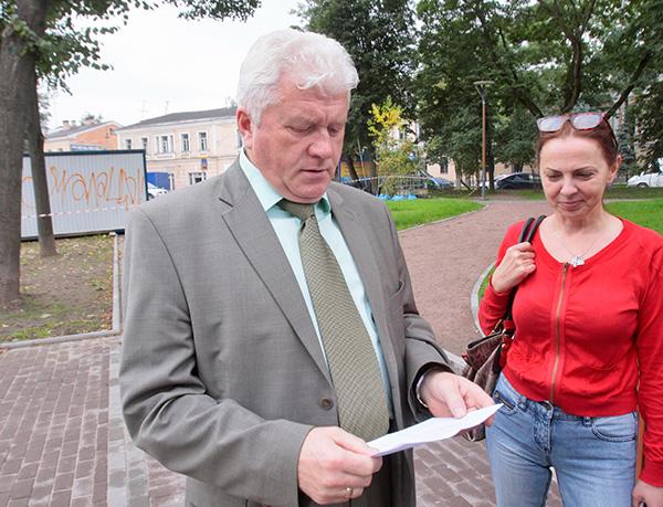 Валерий Волков и Татьяна Артюнина на фоне надписи на строительном вагончике