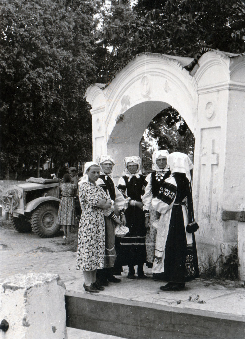 Печоры, начало июля 1941. У входа в Псково-Печерский монастырь. Эта арка находилась рядом с Святыми вратами. Женщины в традиционных национальных костюмах народности сету. Позади виден трофейный английский армейский полноприводный грузовик Bedford MWD 15cwt из PanzerJ?ger Abteilung 158, трофей французской компании.
