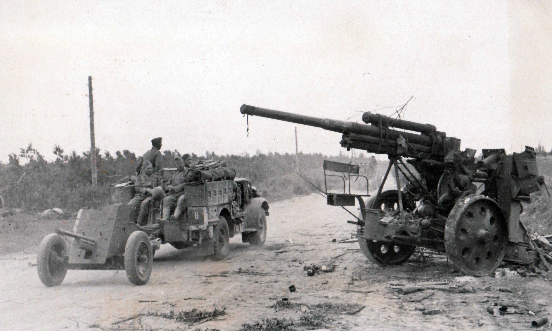 На обочине сгоревший ЗиС-5, буксировавший 76-мм полуавтоматическую зенитную пушку образца 1931 года 3-К на повозке ЗУ-29 из 472-го отдельного зенитного артиллерийского дивизиона 118-й стрелковой дивизии. Мимо проезжает Bedford артиллеристов.