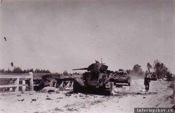На фото: У места второго тарана. На переднем плане сгоревший БТ-7. Башня развернута вправо, видимо он вел огонь по немцу, сбитому в канаву. Взрывом боекомплекта ему оторвало заднюю часть башни. Перед ним на дороге разбросаны его пулеметные диски. За ним БТ-7 без башни и немец 712, сбитый в канаву. Дальше на дороге стоит немецкий Pz.III Ausf.G, а дальше группа танков с предыдущего снимка.