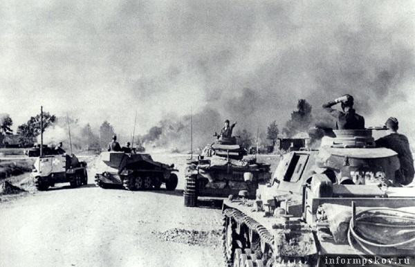 На фото: Командирский танк Bef.Pz.Wg.III Ausf.E II02,  и линейный Pz.III Ausf.G II03 штабной роты 2-го батальона 1-го танкового полка 1-й танковой дивизии подъезжают к перекрестку в Соловьях. Бой в самом разгаре. Впереди горящие танки, дома. Слева в кадре горящий БТ-7, повернувший на перекрестке в сторону Туховика.