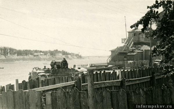 На фото: Переправу прикрывает самоходная зенитка 2-cm Flak-30 на базе полугусеничного тягача Demag Sd.Kfz.10. Справа здание станции ОСВОД, построенное в 1929 году. Вдалеке виднеется взорванный железнодорожный мост.
