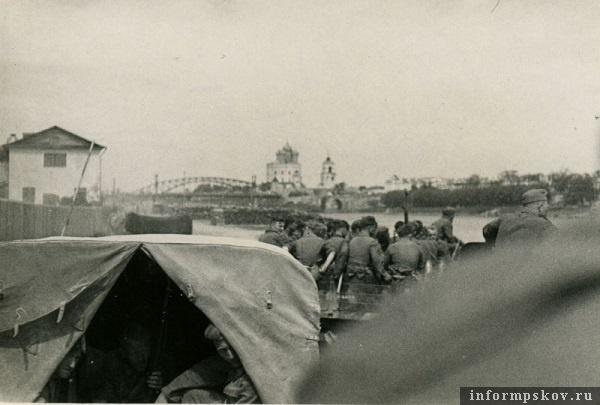 На фото: Спустившись к реке по ул. Лагерной, колонна выезжает к понтонному мосту. В кадре взорванный мост Красной армии, слева здание Псковского речного порта.