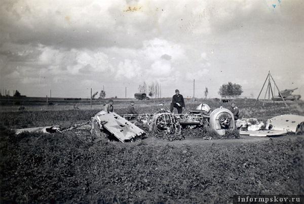 На фото: Самолет сел у шоссе Остров-Псков, на северной окраине Острова. Сейчас это примерно район автозаправочной станции Сургутнефтегаз на въезде в Остров со стороны Пскова. Позади виден подбитый танк КВ-2 3-й танковой дивизии, участвовавшей в атаке на Остров 5-го июля 1941 г.