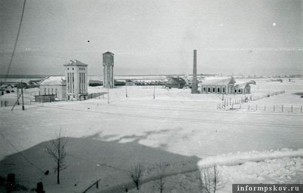 На фото: Фото сделано из одного из домов командного состава. В них жили немцы. По тени видно, что из труб идет дым, здание отапливается. В кадре водонапорная башня городка. Лагерь военнопленных левее.