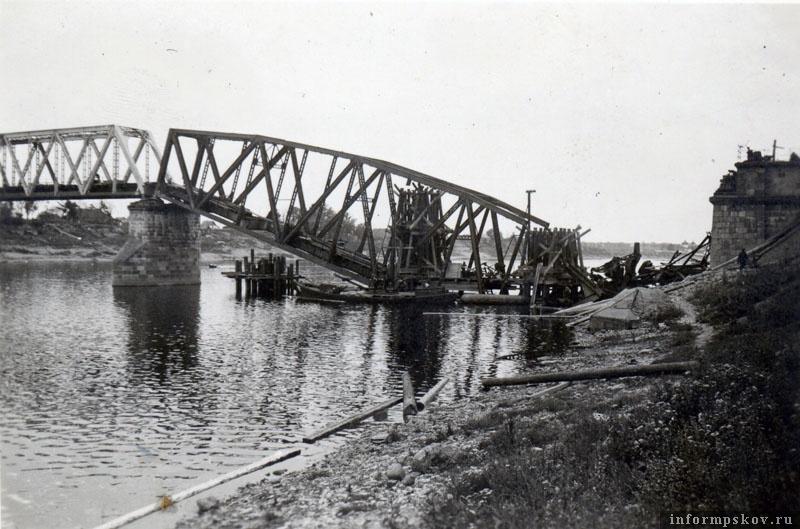 На фото: Железнодорожный мост был стратегически важным для перевозок под Ленинград. Немцы незамедлительно приступили к его восстановлению. Первоначально временные устои были возведены прямо поверх взорванной фермы. Фото из коллекции Андрея Иванова.