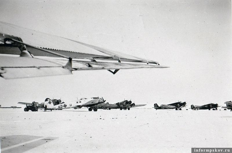 На фото: Хейнкель He.111 из KG.4 и группа Юнкерсов» на аэродроме Остров. Зима 1942 года.