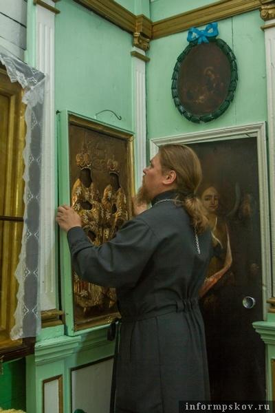 На фото:отец Павел снимает со стены икону Бориса и Глеба