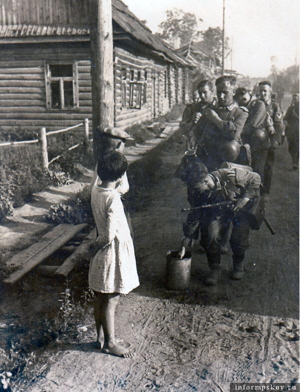 На фото: В одной из деревень. Дети вынесли воду проходящим немецким солдатам.