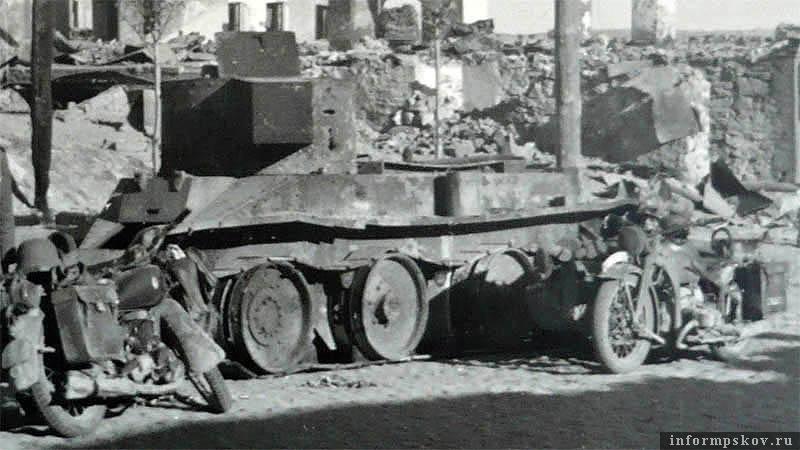 На фото: Немецкие мотоциклы у сгоревшего БТ-5 разведроты 25-го танкового полка на улице Карла Маркса в Острове.