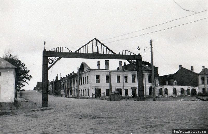На фото: На выезде с Торговой площади в сторону Пскова стояла вот такая арка. Немцы очень любили ее фотографировать. На горке виден сгоревший БТ-5 разведроты 25-го танкового полка