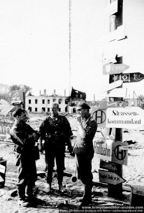 На фото: Немцы у этого же указателя. Фото сделано фотографом SS-Kriegsberichter Baumann'ом (дивизия СС Мертвая голова). US National Archives and Records Administration (NARA), с сайта www.kriegsberichter-archive.com